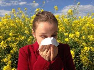 woman sneezing surrounded by flowers, eye allergies - Eye Doctor, Waco, TX